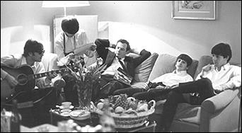 The Beatles relax in their hotel room at the George V in Paris, France, circa January 1964. Left to right: John Lennon, George Harrison, Brian Epstein, Ringo Starr and Paul McCartney.