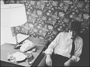 John Lennon looks stressed out and forlorn in his Chicago hotel room, waiting to go to the Beatles press conference where he will be forced to apologize for his statement about The Beatles being more popular than Christ.